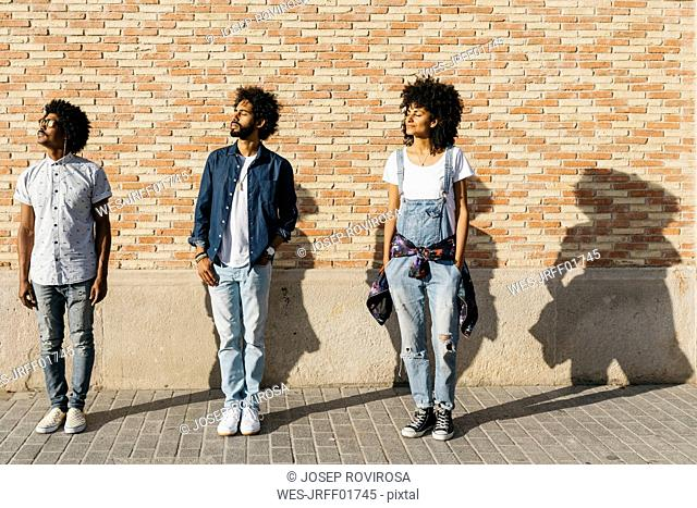 Three friends standing in front of a brick wall sunbathing