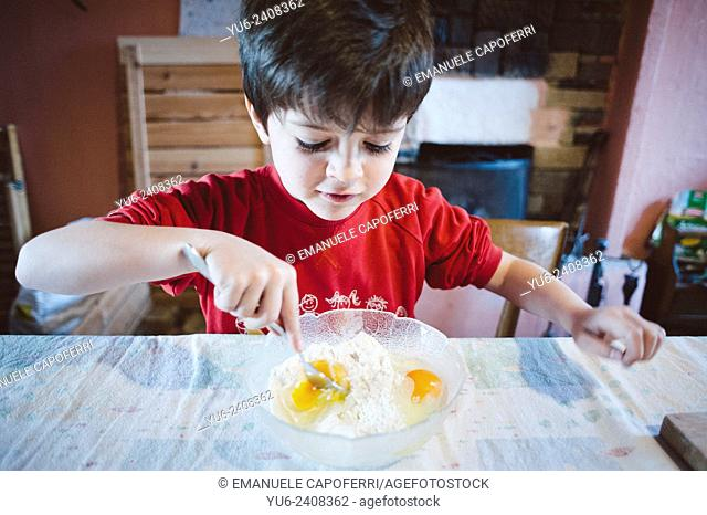 Child in the kitchen mixing flour and eggs