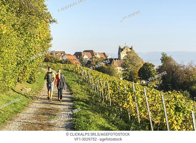 Couple walking on a pathway towards the town center. Meersburg, Baden-Württemberg, Germany