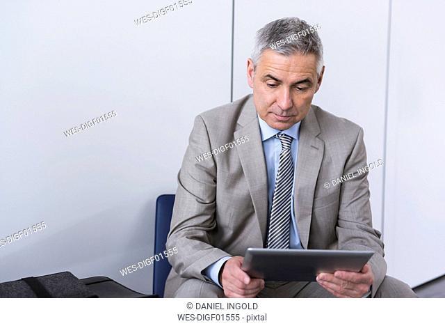 Portrait of a mature businessman, using digital tablet
