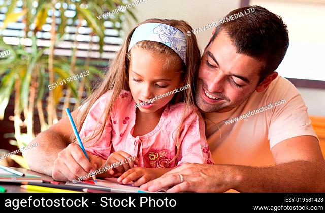 Delighted father helping her daughter for homework