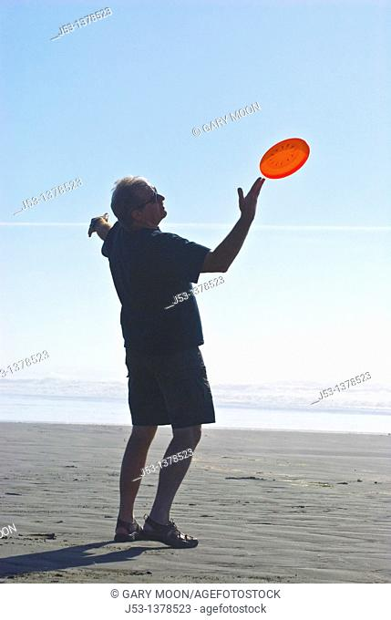 Man playing freestyle frisbee on California beach