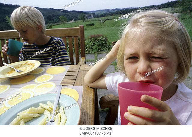 A little girl and a boy, 1-5 years old, sitting in the garden, on the terrace, drinking juice and eating pasta