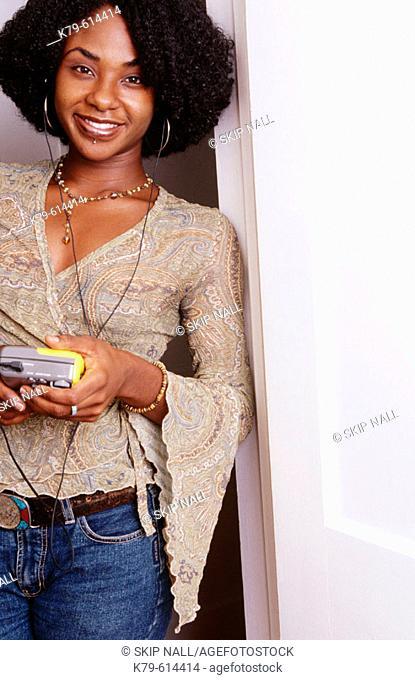 Young black woman standing in doorway listening to music