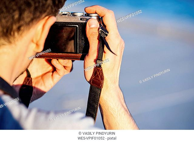 Close-up of young man taking picture with old-fashioned camera