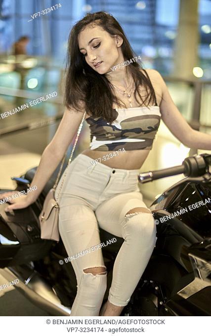fashionable woman sitting on motorbike