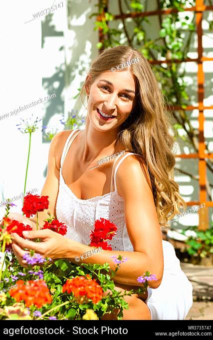 Woman gardener looking at her flowers in the garden