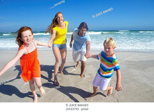 Happy family running toward camera, holding hands, on sunny beach