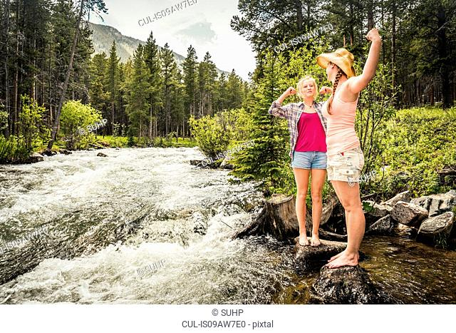 Young woman and teenage girl flexing muscles in forest river, Red Lodge, Montana, USA