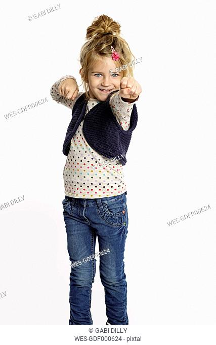 Blond little girl in defence pose standing in front of white background