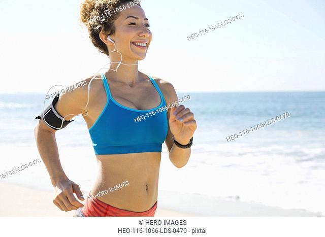 Female jogger listening to music on beach