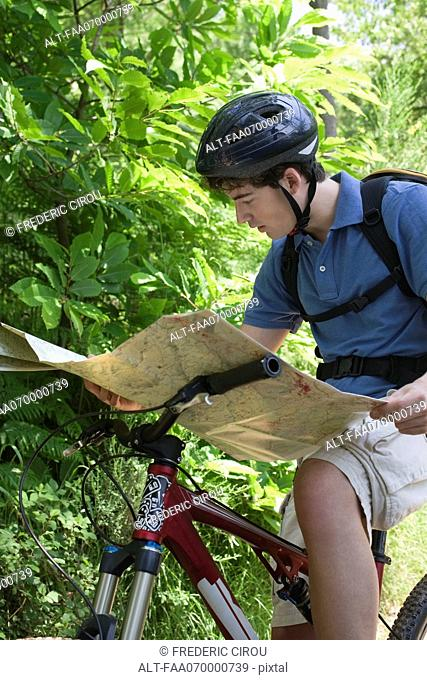 Man reading map on bicycle