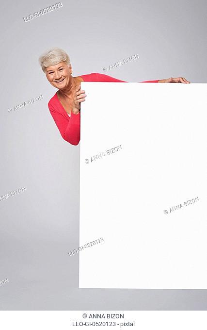 Senior woman standing behind of white billboard. Debica, Poland