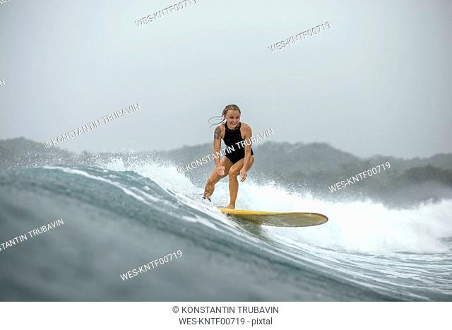 Indonesia, Java, woman surfing