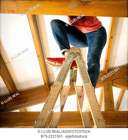 Unrecognizable woman legs on a ladder inside a house with wooden beams