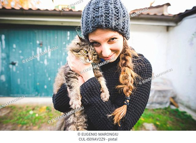 Young woman wearing knit hat snuggling cat, looking at camera smiling