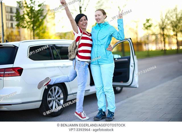 two adventurous women in front of car with open door, ready to start adventure, in Munich, Germany