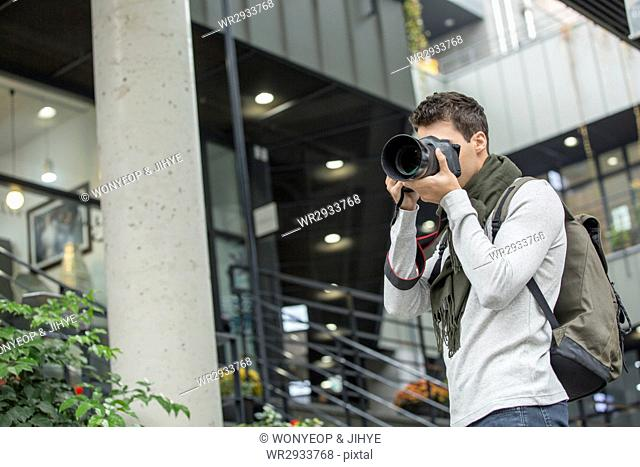 Young male tourist taking photos