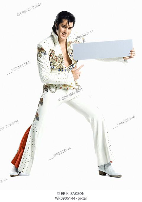 Portrait of an Elvis impersonator holding a blank sign
