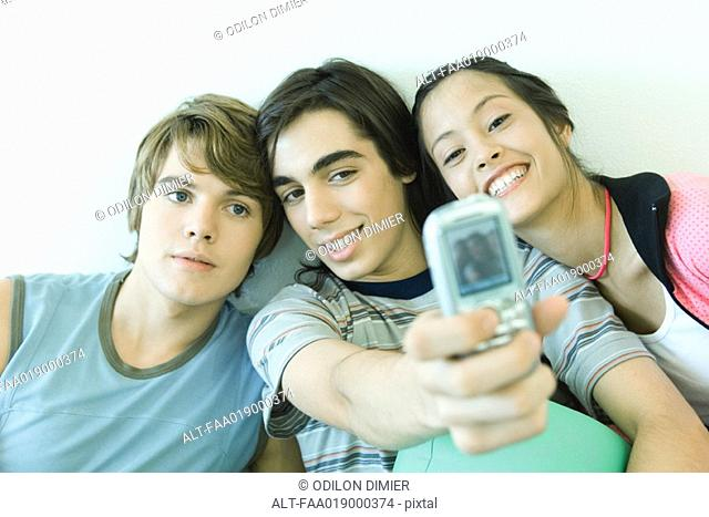 Three teen friends taking self portrait with cell phone