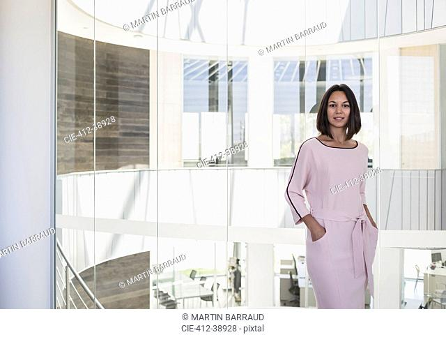 Portrait confident businesswoman standing at window in modern office