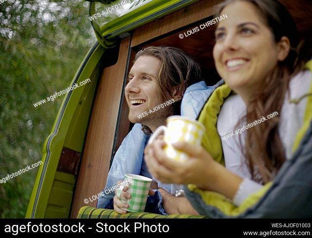 Couple having coffee in campervan while enjoying road trip