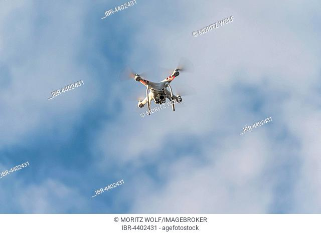 Quadcopter, drone with camera flying in front of blue sky, DJI Phantom 3
