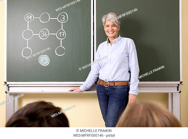 Smiling teacher at blackboard with arithmetic problem