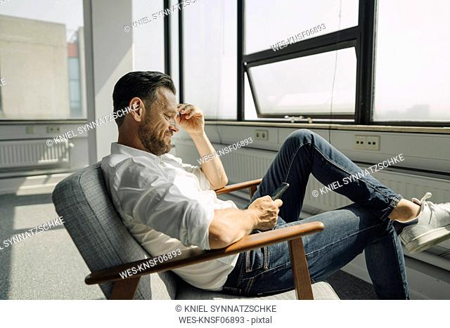Mature businessman using cell phone in empty office