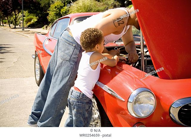 Father and son checking under car hood