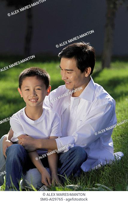 Father and son sitting on grass together