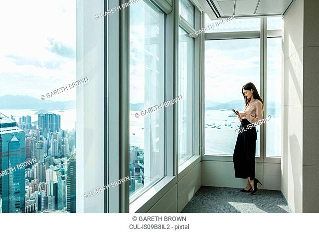 Business woman in skyscraper office window using smartphone