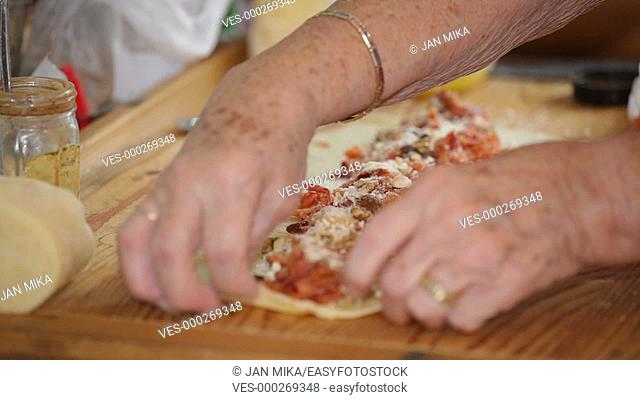 Closeup of senior female hands making apple strudel