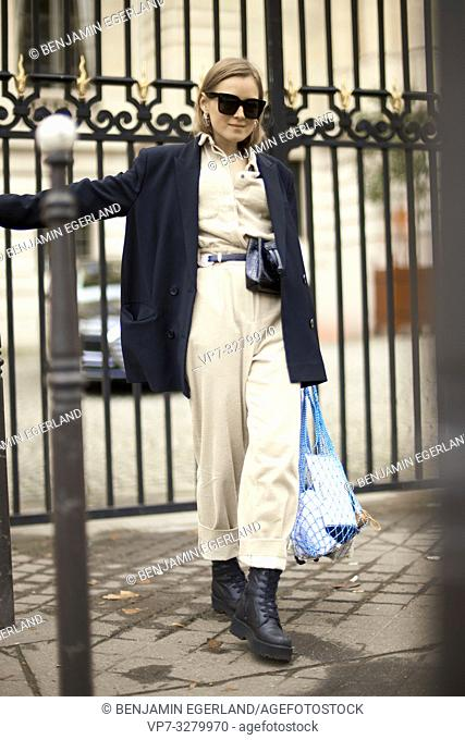 fashionable woman at street during fashion week in front of show entrance, in Paris, France, in Paris, France