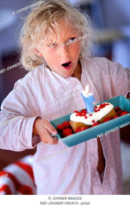 Girl blowing candle on her birthday cake