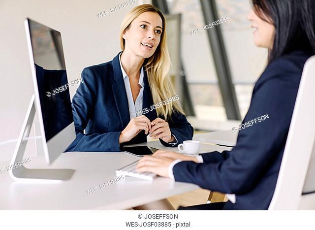 Two businesswomen sitting at desk in office talking
