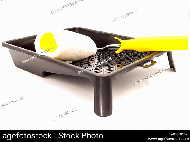 A clean paint roller rests on a black paint tray. Isolated on white background with clipping path