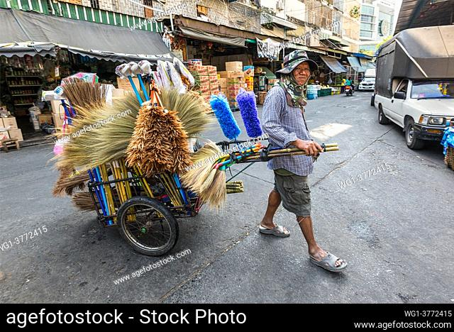 Bangkok, Thailand - December 7, 2019: Street vendor of brooms and feather dusters travels a street with the cart full of goods - selling sweeping brushes from a...