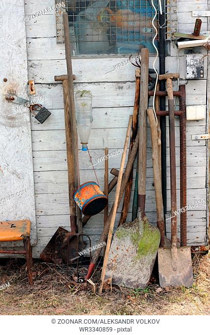 Agricultural tools - shovels, a pitchfork, a rake and a mattock near a rural shed. On the earth it is possible to notice a dead polecat