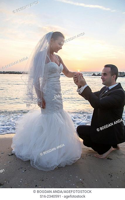Bridegroom puting a ring on his bride's finger at sunrise on the beach