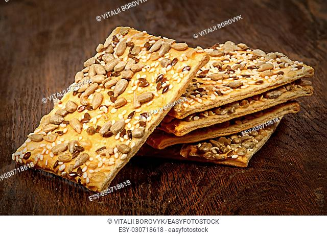 Pile of cereal cookies with seeds on a wooden table