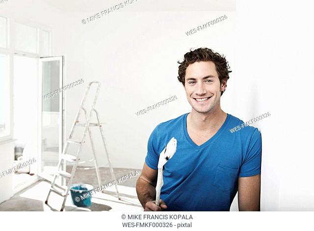 Germany, Cologne, Close up of young man holding paint brush in renovating apartment, smiling, portrait