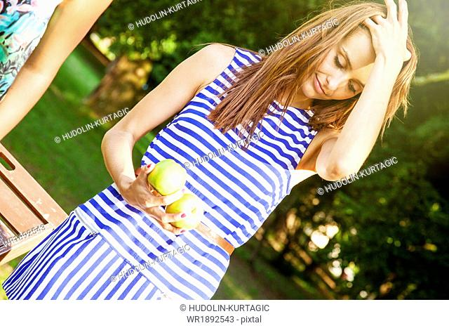 Young woman in striped shirt holding apples in hand