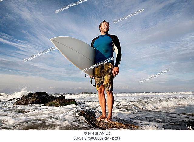 Surfer standing on rocks on beach
