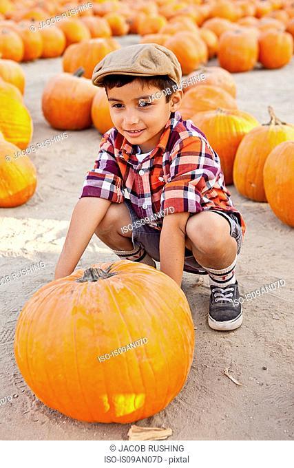 Portrait of boy choosing pumpkin in farmyard