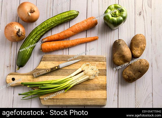 An assortment of vegetables such as onions, carrots, potatoes, and green bell pepper and a cutting board