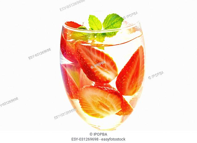 glass delicious refreshing drink of strawberry with mint on on white background, infusioned water, warm color tone