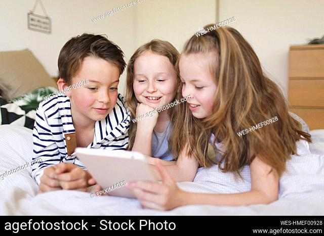 Portrait of boy and his two sisters lying on bed using digital tablet for homeschooling
