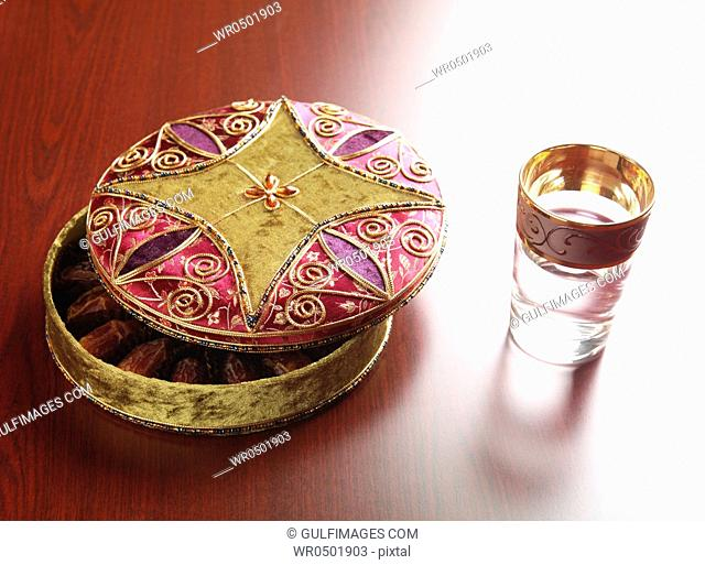 Decorative box with glass of water on wooden surface