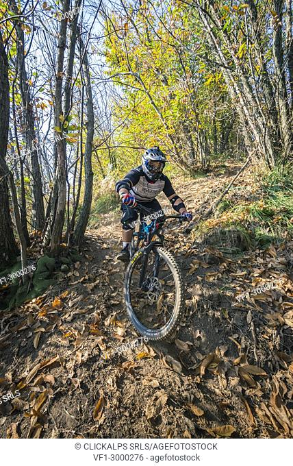 Enduro practice, Pogno, Piedmont, Italy. A cyclist runs an enduro dirt